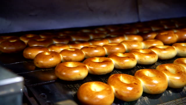 Making of the fresh hot tasty bagels at the backery's factory: plane bagels comes out from the oven. 4K UHD video with panoramic motion. video