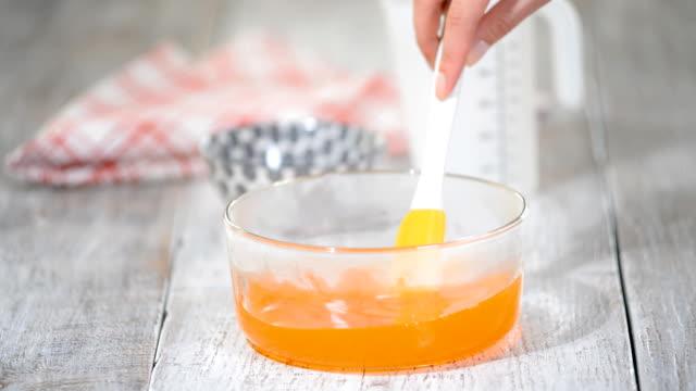 オレンジ ゼリーを作る。ガラスのボウルでゼリーを混ぜます。 - プリン スプーン点の映像素材/bロール