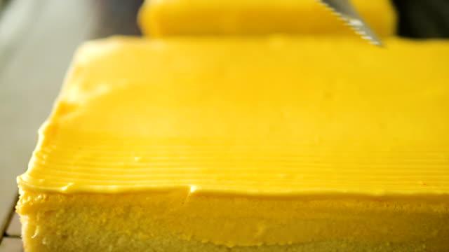 making pattern on yellow cream cake, slow motion. - szpatułka przybór do gotowania filmów i materiałów b-roll
