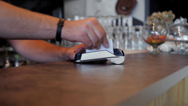 Making payment with credit card and pos terminal, printed check. a coffee shop video