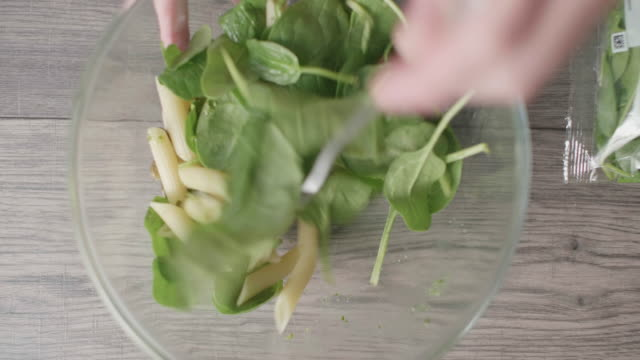 making penne pasta salad with green pesto sauce close up view of making penne pasta with freshness spinach and green pesto salad pesto sauce stock videos & royalty-free footage