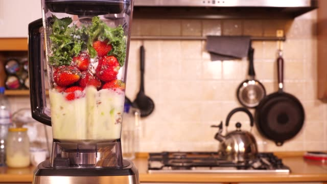 herstellung von kürbis-erdbeerob-feldshake im mixer 4k - grünkohl stock-videos und b-roll-filmmaterial