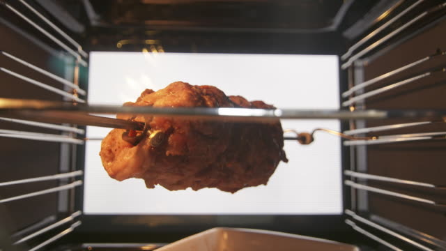 Making roasted pork meat on the rotisserie spit in hot convection oven timelapse
