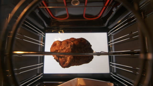Making roasted pork meat on the rotisserie spit in hot convection oven video