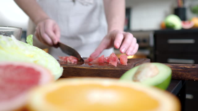 Making salad with grapefruit and avocado