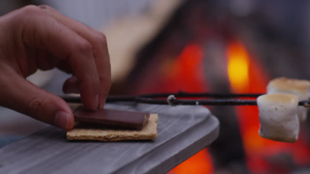 Making smores by outdoor fire. Making smores by outdoor fire. Shot on RED EPIC for high quality 4K, UHD, Ultra HD resolution. marshmallow stock videos & royalty-free footage