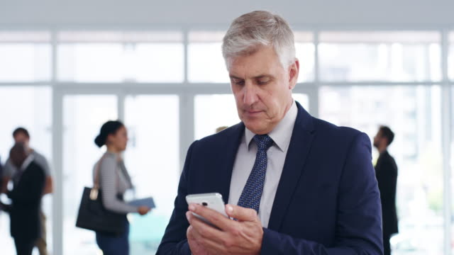 Making space for new business contacts on his phone 4k video footage of a thoughtful mature businessman using a mobile phone at a convention center suit videos stock videos & royalty-free footage