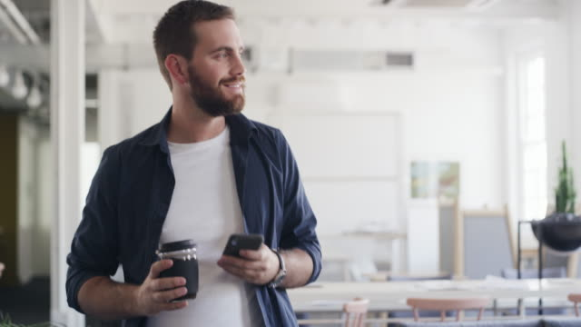 making success happen with coffee and connectivity in hand - distrarre lo sguardo video stock e b–roll