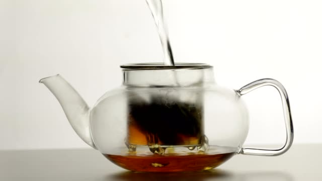 Making tea in a glass teapot Boiling water is being poured on teabags in a glass teapot. Preparing tea. drenched stock videos & royalty-free footage