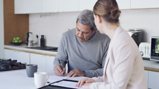 Making the best financial choices with the best advice 4k video footage of a senior man meeting with a consultant to discuss paperwork at home form filling stock videos & royalty-free footage