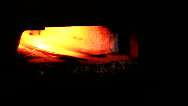 Making the sword out of metal at the forge. Heating of metal billets in the furnace. Closeup view. Making the sword out of metal at the forge. Heating of metal billets in the furnace. Closeup view foundry stock videos & royalty-free footage