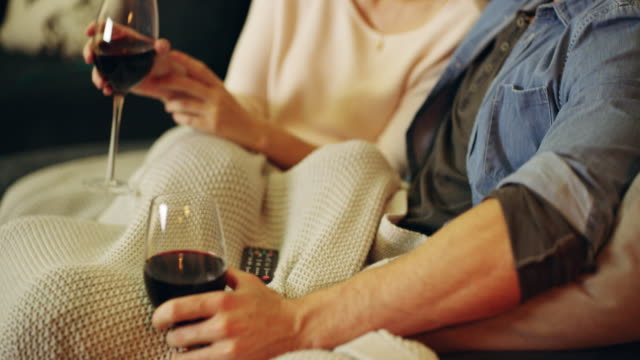 Making time for romance 4K video footage of a happy young couple enjoying a glass of wine during a romantic night at home red wine stock videos & royalty-free footage