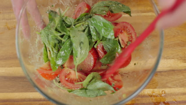 making tomato salad top view of close up shoot making tomato basil salad in a mixing bowl tomato salad stock videos & royalty-free footage