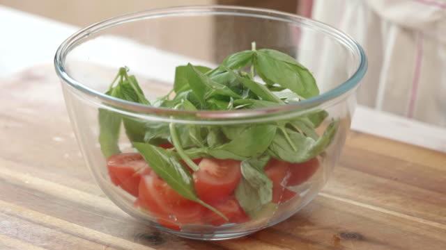 making tomato salad close up shoot making tomato basil salad in a mixing bowl tomato salad stock videos & royalty-free footage