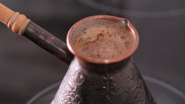 Making Turkish coffee in copper jezve over electric stove