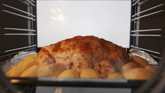 vídeos de stock e filmes b-roll de making whole roasted chicken with potatoes baked in the oven timelapse - inteiro