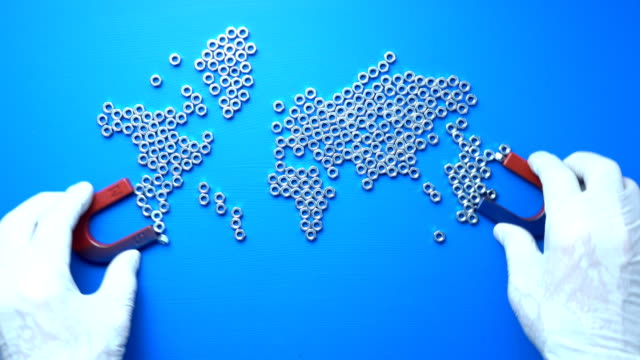 Making World Map With Screw Nuts And Magnets On Blue Background