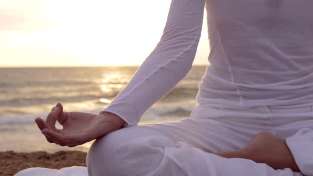 making yoga position at the sunset on the beach: sea, woman, lonely, meditation video