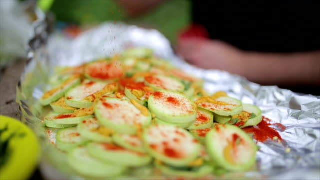 Making  zucchini ,sprinkling paprika on it Making of vegeterian meal outdoors in the nature paprika stock videos & royalty-free footage