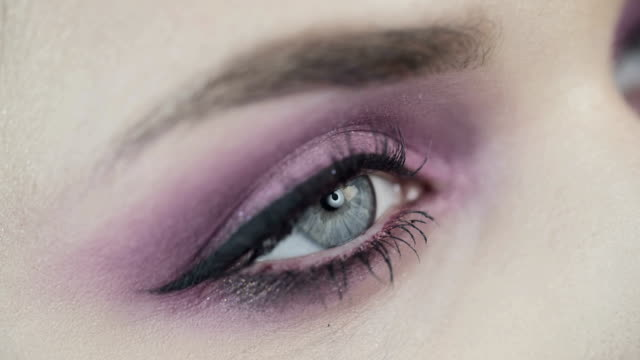 Makro shot of beautiful eye of girl with pink shades. Pink make up. Makro shot of beautiful eye of girl with pink shades. Girl opens her eye. Looks at up. Clear skin. eyeliner stock videos & royalty-free footage