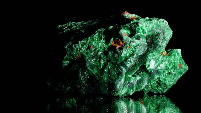 Malachite turning on black Malachite mineral turning on black, reflecting surface copper stock videos & royalty-free footage