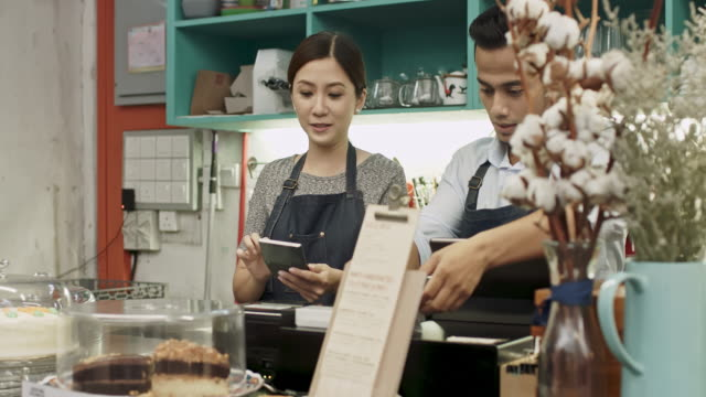 Malay business couple working at coffee shop Malay business couple working at coffee shop, they are going through all the receipts of the day. east asian ethnicity stock videos & royalty-free footage