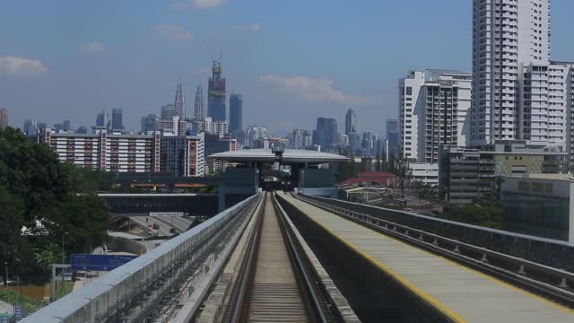 stockvideo's en b-roll-footage met maleisië mrt (mass rapid transit) trein met achtergrond van kuala lumpur stad - maleisië
