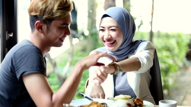vidéos et rushes de couple malaisien dîner ensemble au café en plein air - admiration