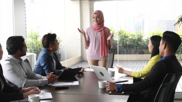 malaysian woman in hijab talking to colleagues - etnia malese video stock e b–roll