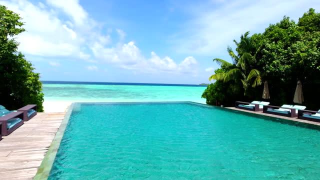 malediven, blauer himmel, türkisfarbenes meer, weißer sand und grüne palmen. - sun chair stock-videos und b-roll-filmmaterial