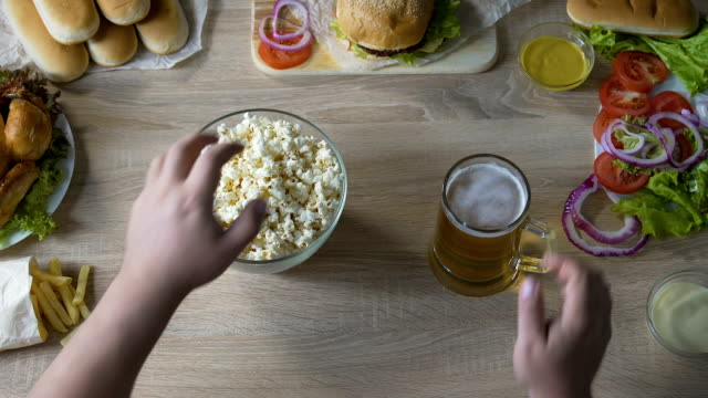 Male abusing harmful food, eating full arms of popcorn and drinking lots of beer video
