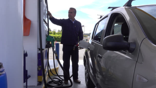 Male adult stopping at gas station to refuel his car video
