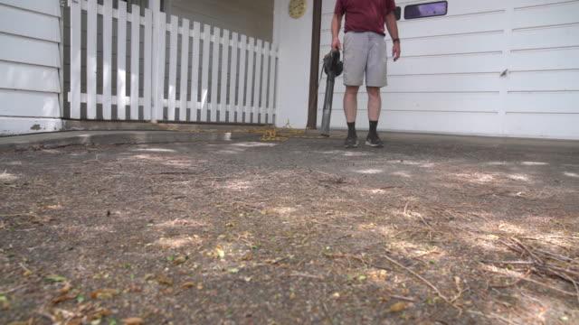 vidéos et rushes de adulte mâle utilisant un souffleur de feuille électrique pour enlever les graines, les feuilles et les bâtons d'orme de l'allée pour le nettoyage de ressort - vidéos de rallonge électrique