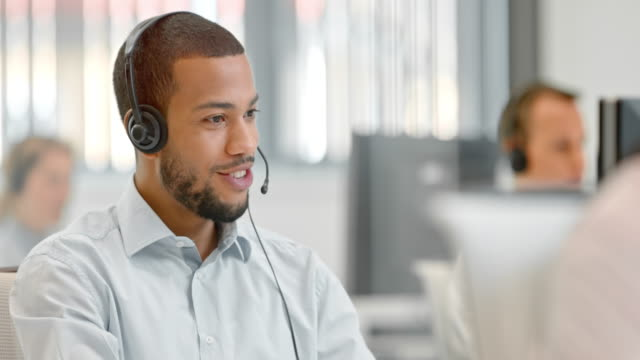 TU Male African American telephone operator answering a call Medium tilt up dolly shot of an African-American telephone operator answering a call at his desk in the call center. call centre videos stock videos & royalty-free footage