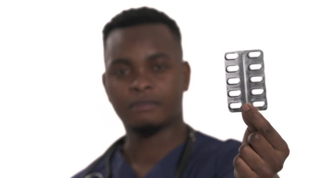Male African doctor holding blister pack with pills. Healthcare and pharmacy concept. Focus changing shot