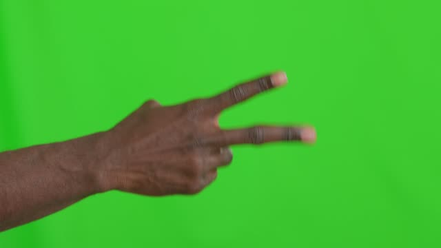 male african hand showing rock paper scissors game - forbici video stock e b–roll