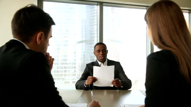 Male afro american job applicant at job interview, handshaking, introducing video
