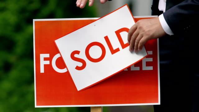 männliche agent einstellung verkauft zeichen im freien, immobilienunternehmen, hausbesitz - schild stock-videos und b-roll-filmmaterial