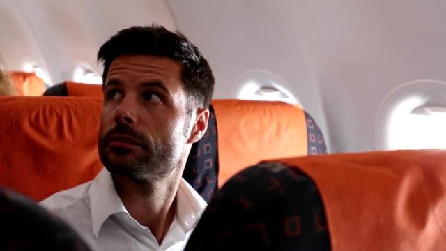사람들이 비행기를 입력 하는 사람을 기다리고 남성 비행기 여객. 비행기의 출발을 기다리는 남자. 비행기 안에서 기다리는 사람 - airplane seat 스톡 비디오 및 b-롤 화면