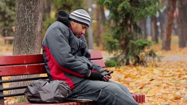 Male alcohol addict having a nap on bench in autumn park with bottle in hand