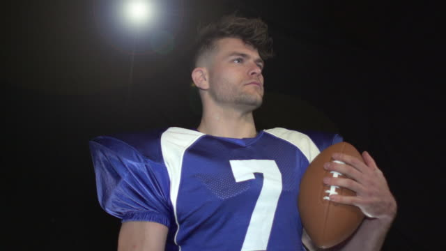 Male American Football Player Portrait pose - Super Slow Motion 180 degree rotation Stock HD video clip footage of a male American Football Player. Filmed in Super Slow motion, the camera rotates 180 degrees around the player. Black Background. Indoors pre game stock videos & royalty-free footage