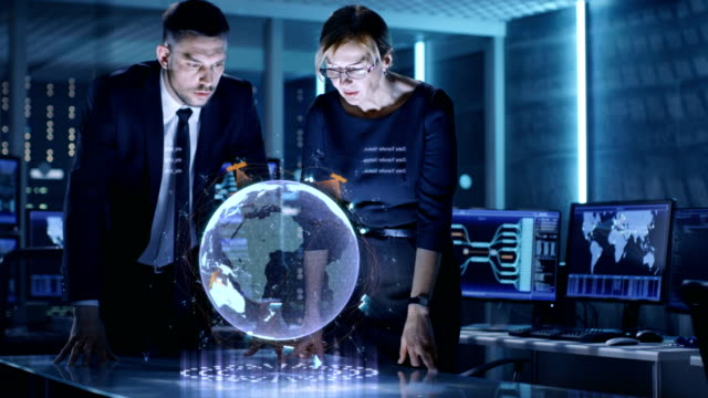 Male and Female Agents Use Mixed Media Holographic Table for Satellite Surveillance. In the Monitoring Room of Special International Security Unit Tracking Targets.