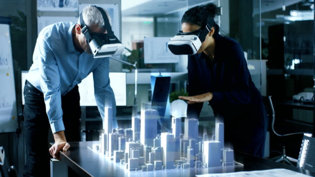 male and female architects wearing  augmented reality headsets work with 3d city model. high tech office professional people use virtual reality modeling software application. - progettare video stock e b–roll