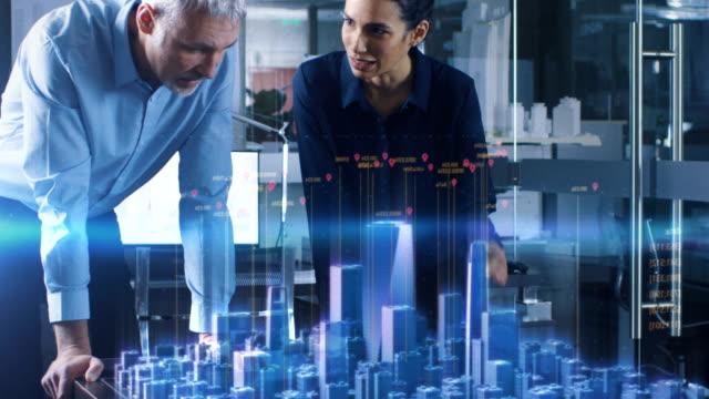 ホログラフィック拡張現実感三次元都市モデルと男性と女性建築家に仕事。技術的に高度なオフィスの専門家の人々 は、仮想現実モデリング ソフトウェア アプリケーションを使用します。 - ホログラム点の映像素材/bロール