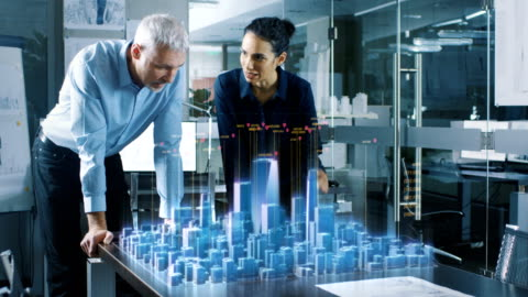 männliche und weibliche architekten arbeiten mit holographischen augmented reality 3d stadtmodell. technologisch fortschrittliche büro professionelle leute verwenden virtual reality modeling software-anwendung. - hologramm stock-videos und b-roll-filmmaterial
