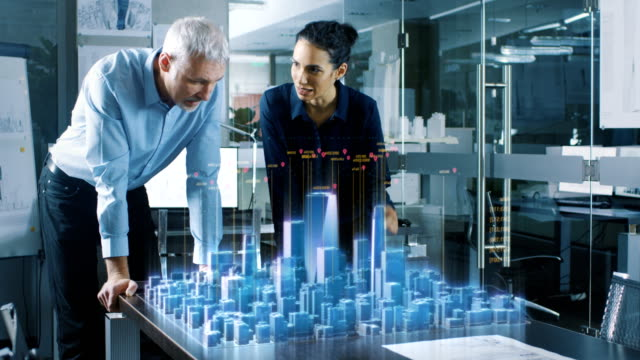male and female architects work with holographic augmented reality 3d city model. technologically advanced office professional people use virtual reality modeling software application. - progettare video stock e b–roll