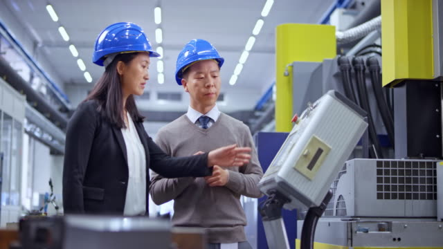 DS Male and female Asian engineer having a discussion standing by the machine in the factory Wide dolly shot of an Asian female engineer talking to her male colleague as they stand next to the machine in the factory. Shot in Slovenia. manufacturing equipment stock videos & royalty-free footage