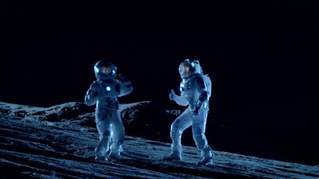 Astronautas masculinos y femeninos con baile de trajes espaciales en la superficie del planeta alienígena. La humanidad colonización celebración temática espacial. - vídeo