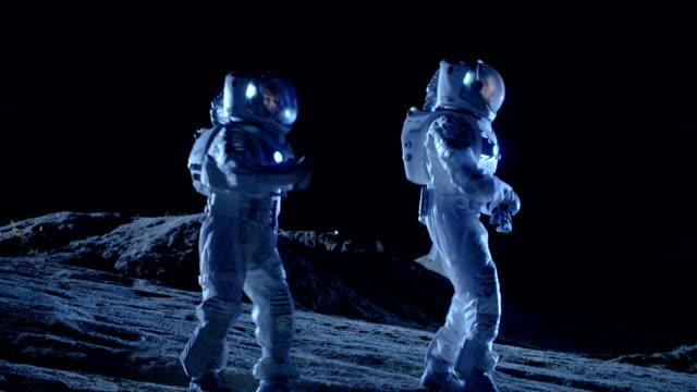 männliche und weibliche astronauten tragen raumanzüge tanz auf der oberfläche des fremden planeten. menschheit besiedeln raum feier thema. - raumanzug stock-videos und b-roll-filmmaterial