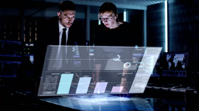 Male and Female Business Managers Use Touchscreen Interactive 3D Panel in Big Monitoring Room Full of Computers with Animated Screens. Male and Female Business Managers Use Touchscreen Interactive 3D Panel in Big Monitoring Room Full of Computers with Animated Screens. Shot on RED EPIC-W 8K Helium Cinema Camera. hologram stock videos & royalty-free footage